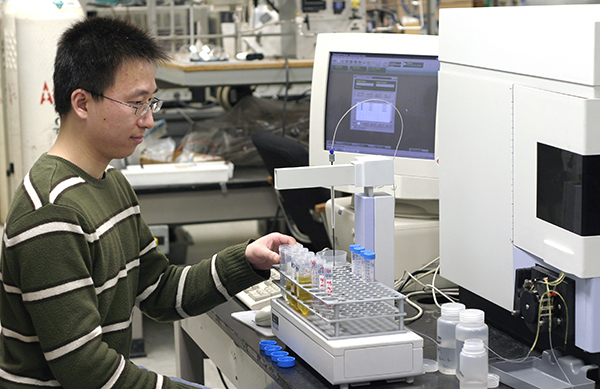 student working with chemicals at a computer workstation